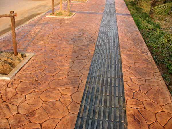 ),初次施工压花地坪,建议使用自拌混凝土,方便掌握压花速度,如果使用商品混凝土一定要沟通好浇注速度。  2、压印花纹,在混凝土初凝时依次铺上脱模布(避免模具粘上混凝土),使用模具压印花纹。初凝即混凝土开始失去塑性时,在初凝时压印可避免混凝土泌水。  (大面积压花)  (压制模板)  (压印后混凝土) 3、养护混凝土,压花地坪是在混凝土的基础上做出的,所以为防止其开裂混凝土养护是非常必要的。养护方法包括洒水、覆盖湿麻袋等。  4、压花着色,混凝土养护14至28天后,使用农用喷雾器喷涂着色,着色前保证压花地面